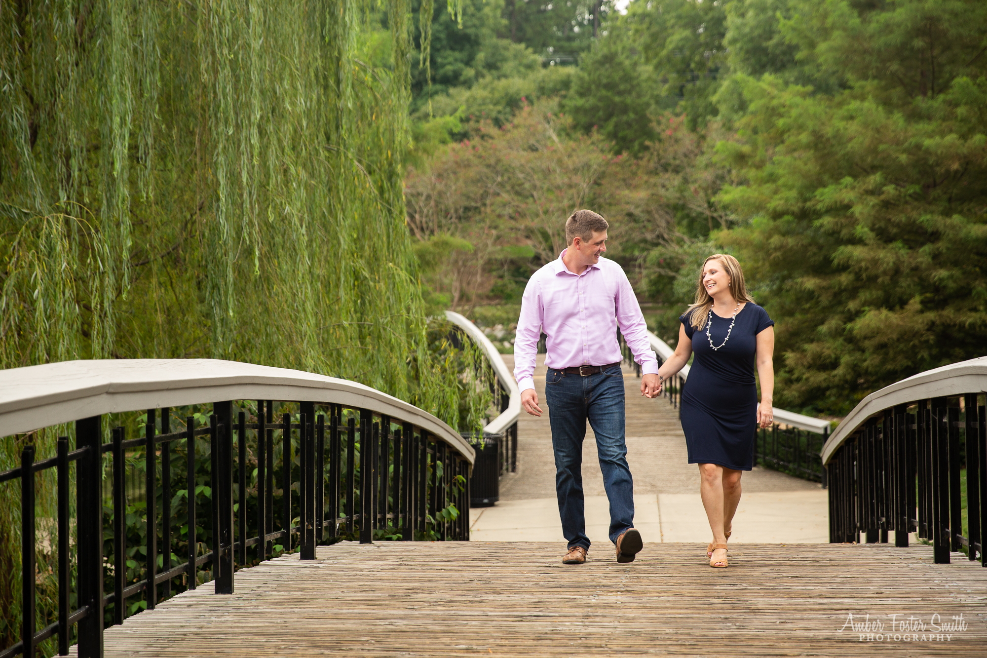 Engaged couple walking over a bridge at Pullen Park