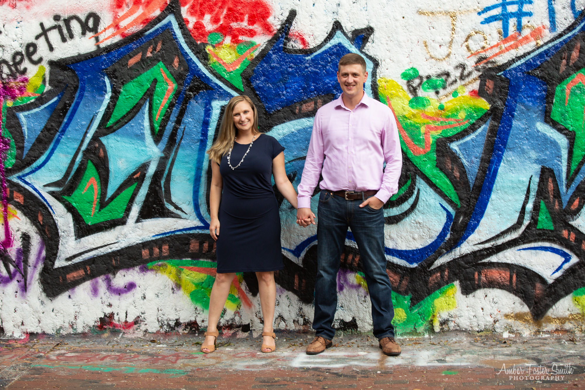 Engaged couple standing in front of a graffiti wall at the Free Expression Tunnel