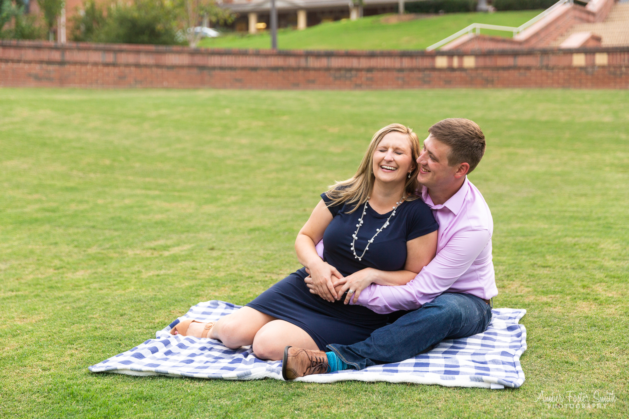 Engaged couple sitting on a blanket in the Court of Carolinas