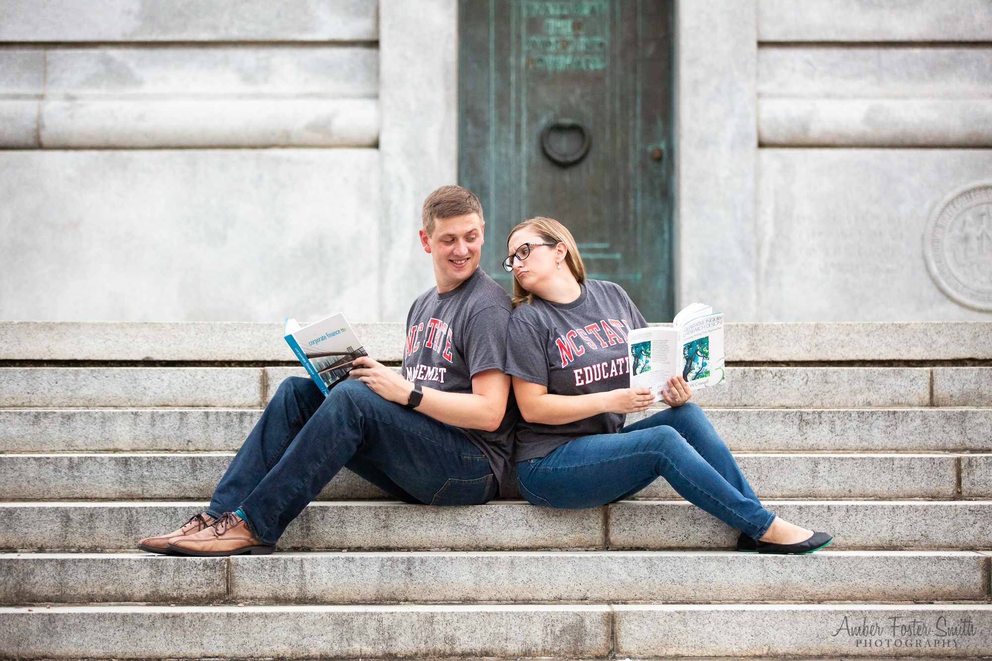 Engaged couple sitting on the steps of the NCSU Bell Tower