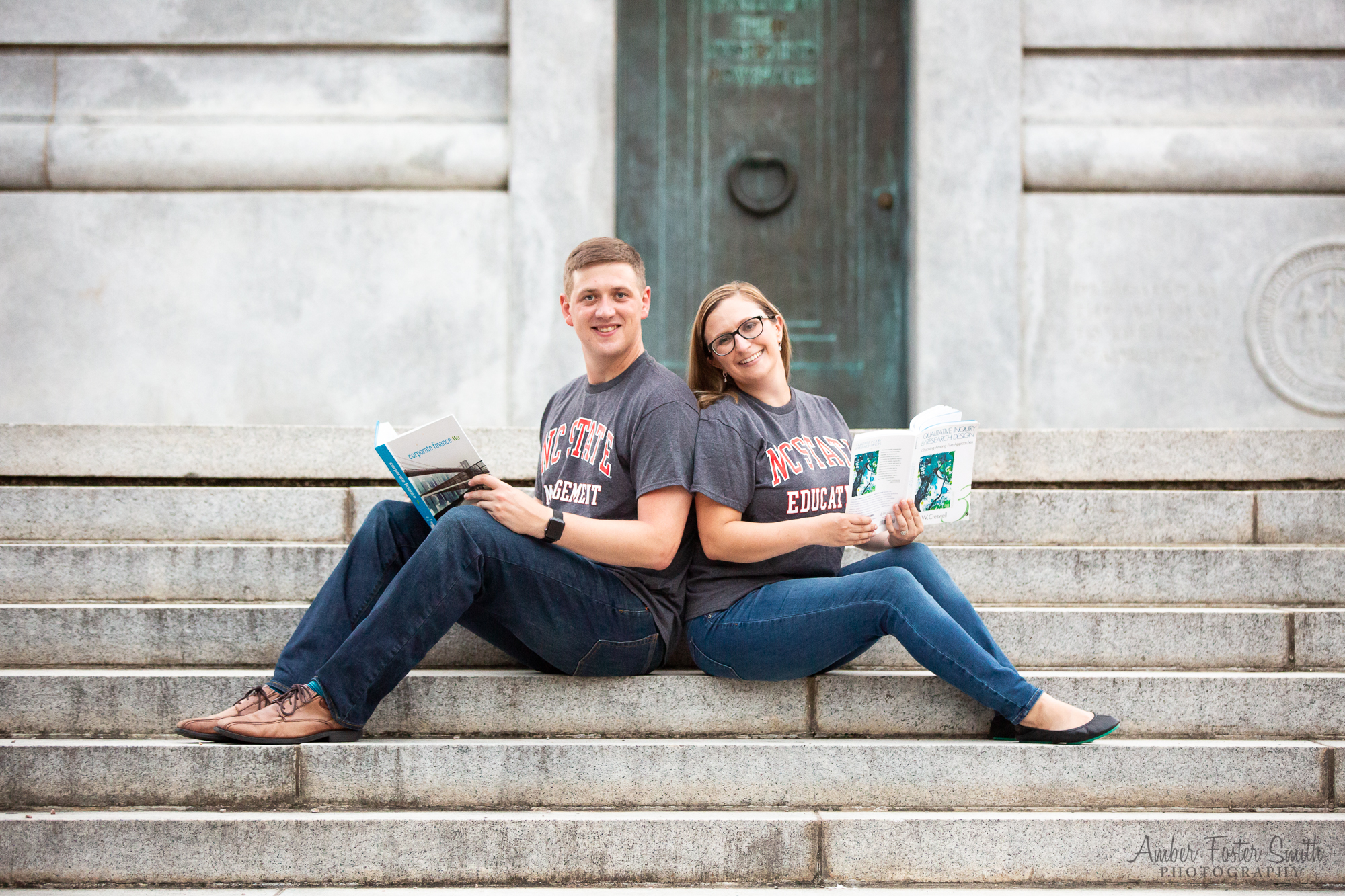Engaged couple sitting on the steps of the NCSU Bell Tower reading books