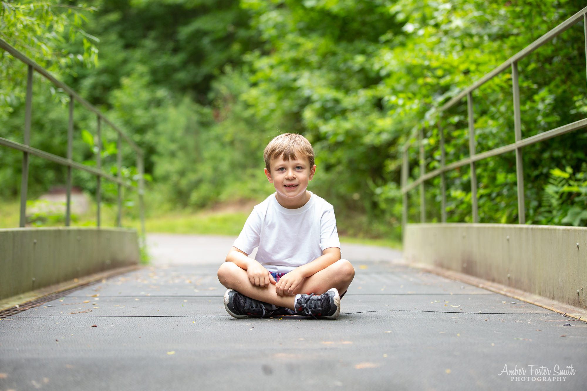 Boy sitting centered on a metal bridge