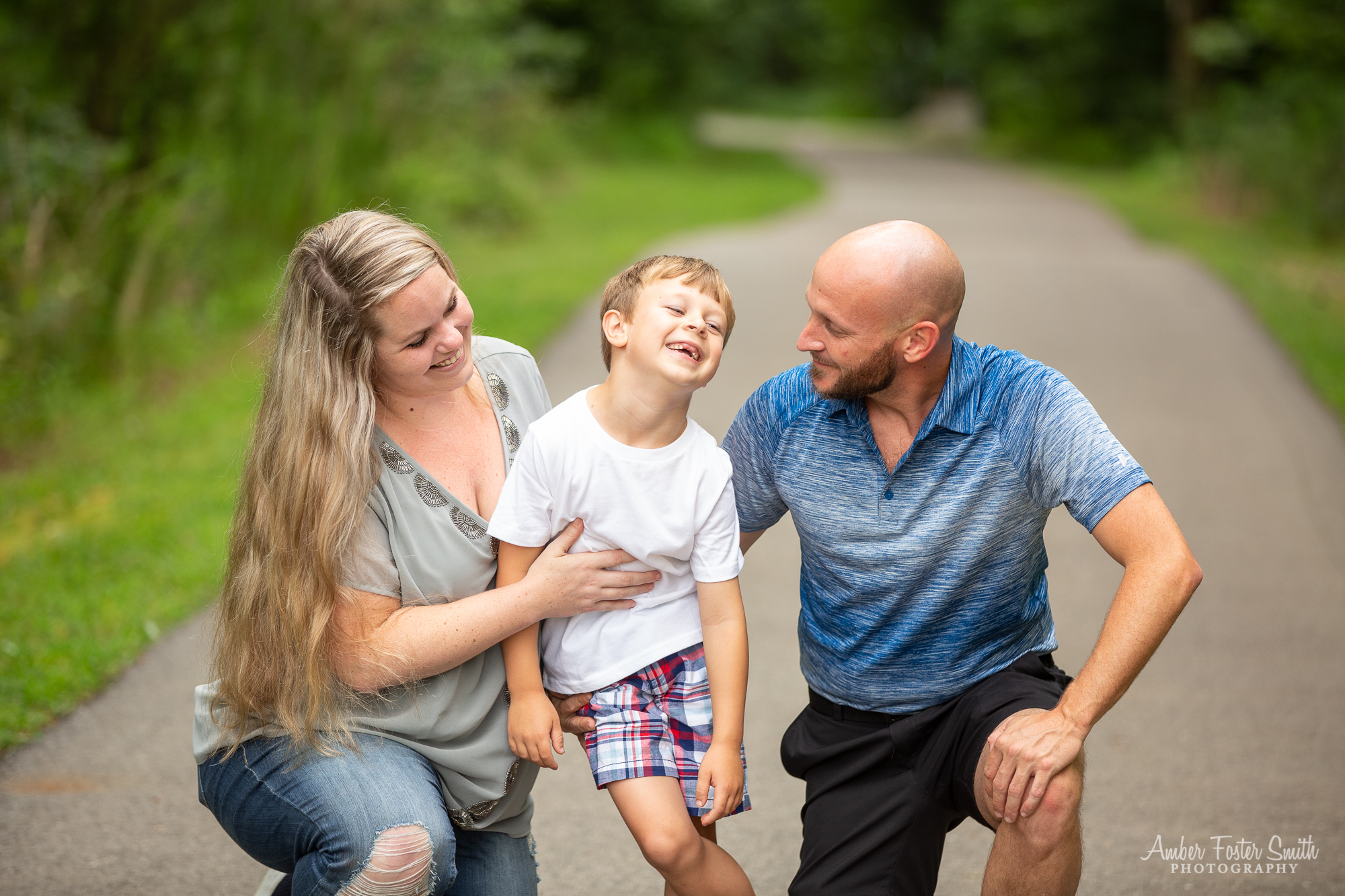 Young boy laughing while dad looks on and woman smiles