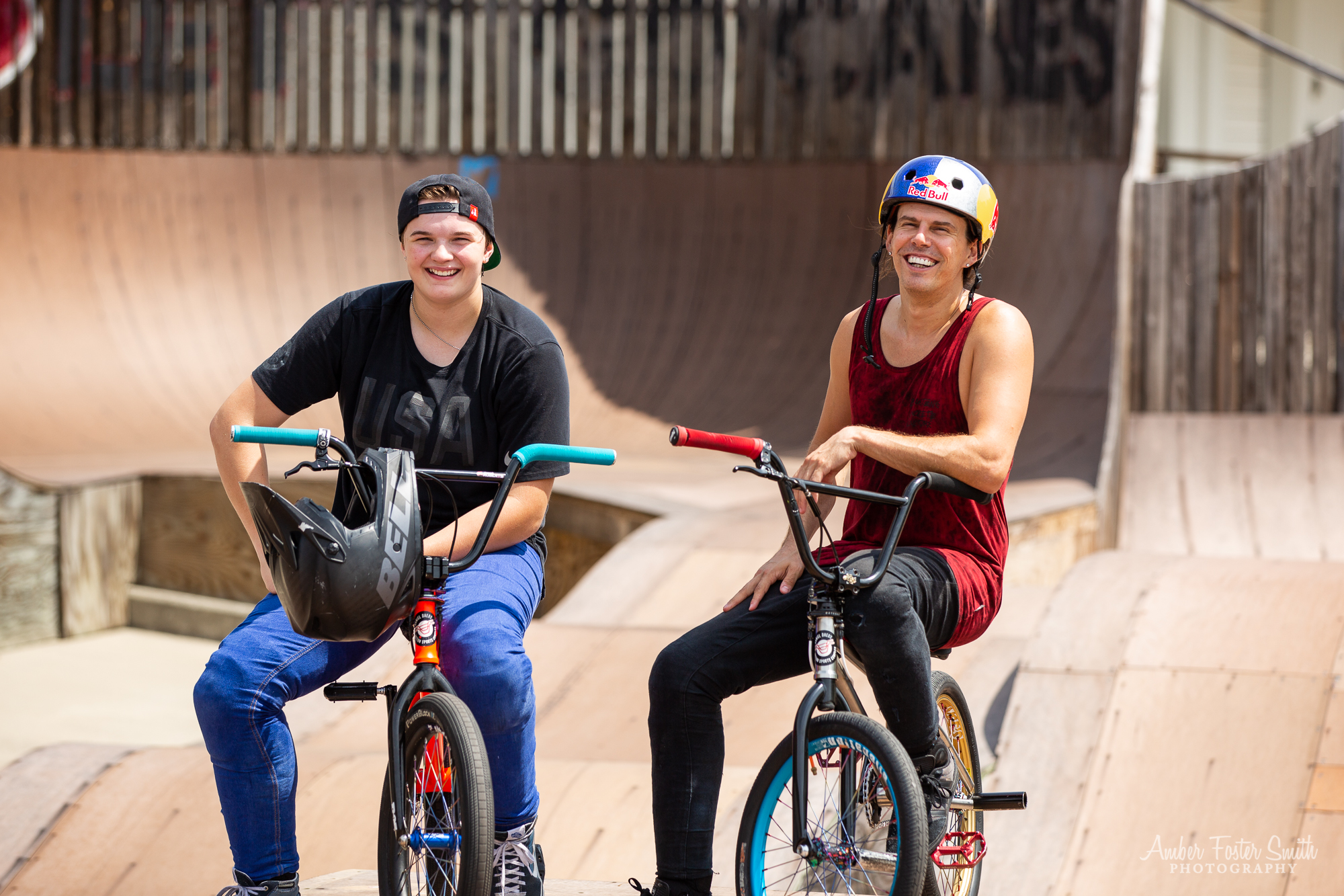 Man and woman sitting on bikes at a skate park