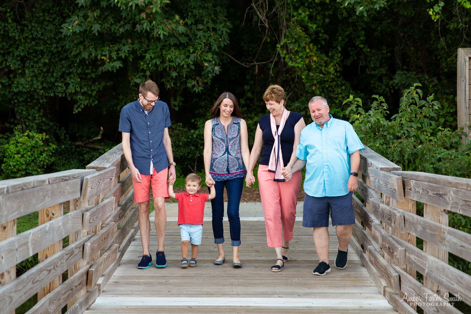 family walking hand in hand on a dock