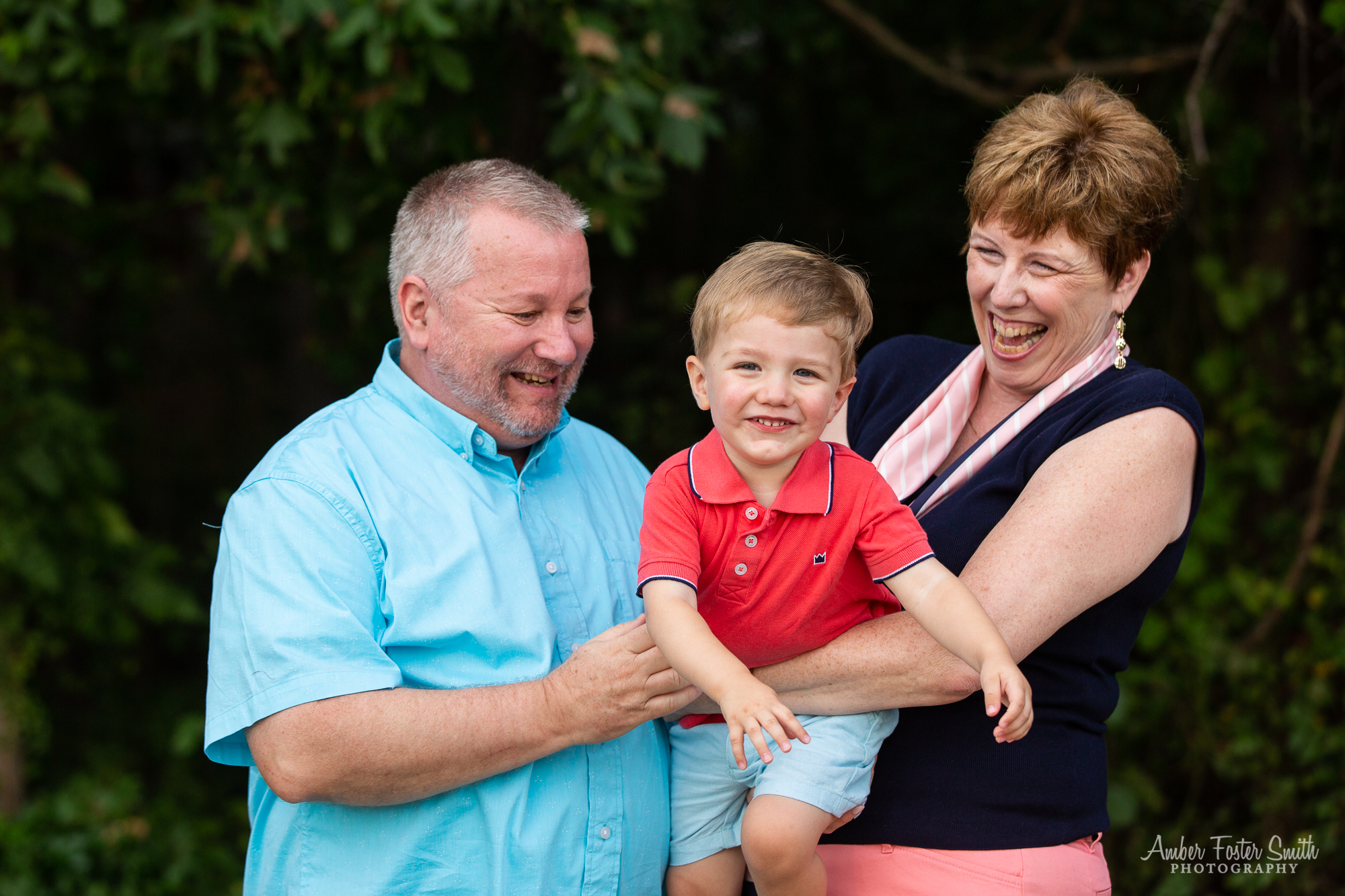grandparents holding giggling little boy