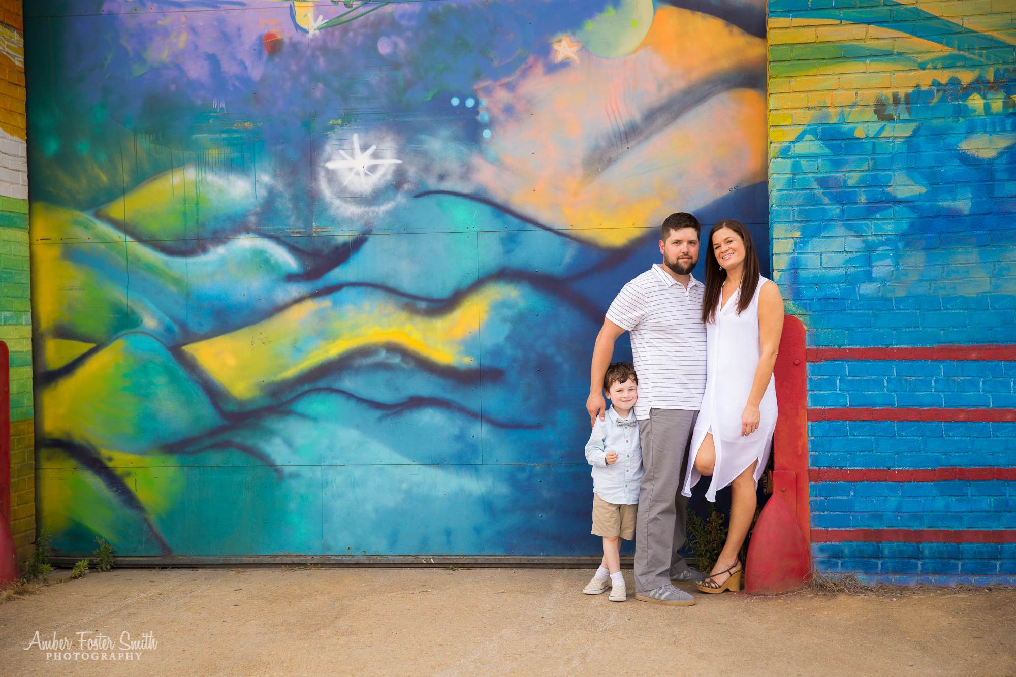 family of three standing against a mural