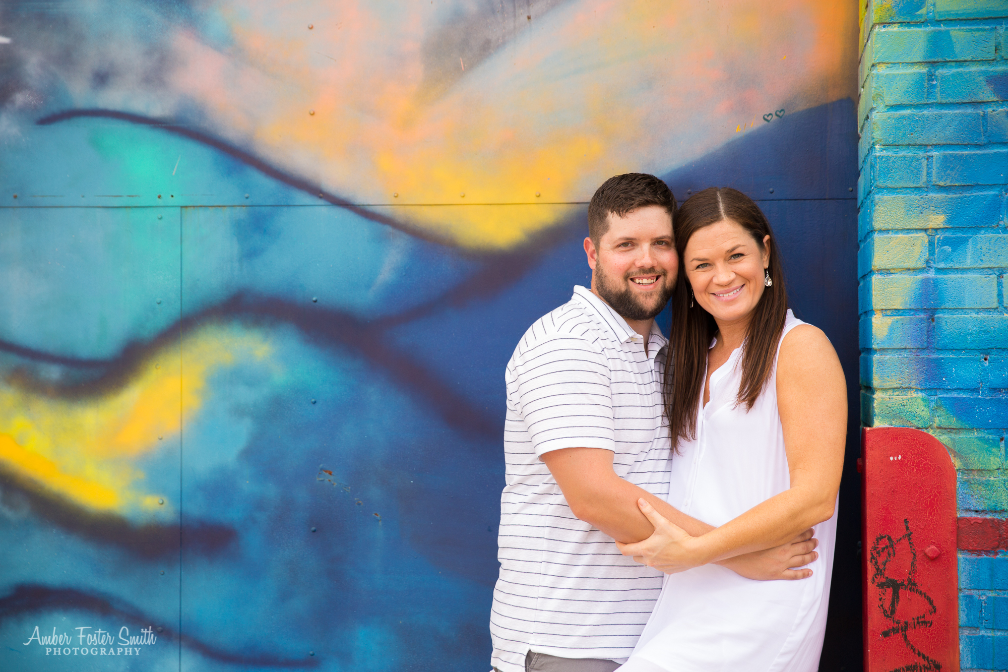mom and dad holding each other in front of a mural