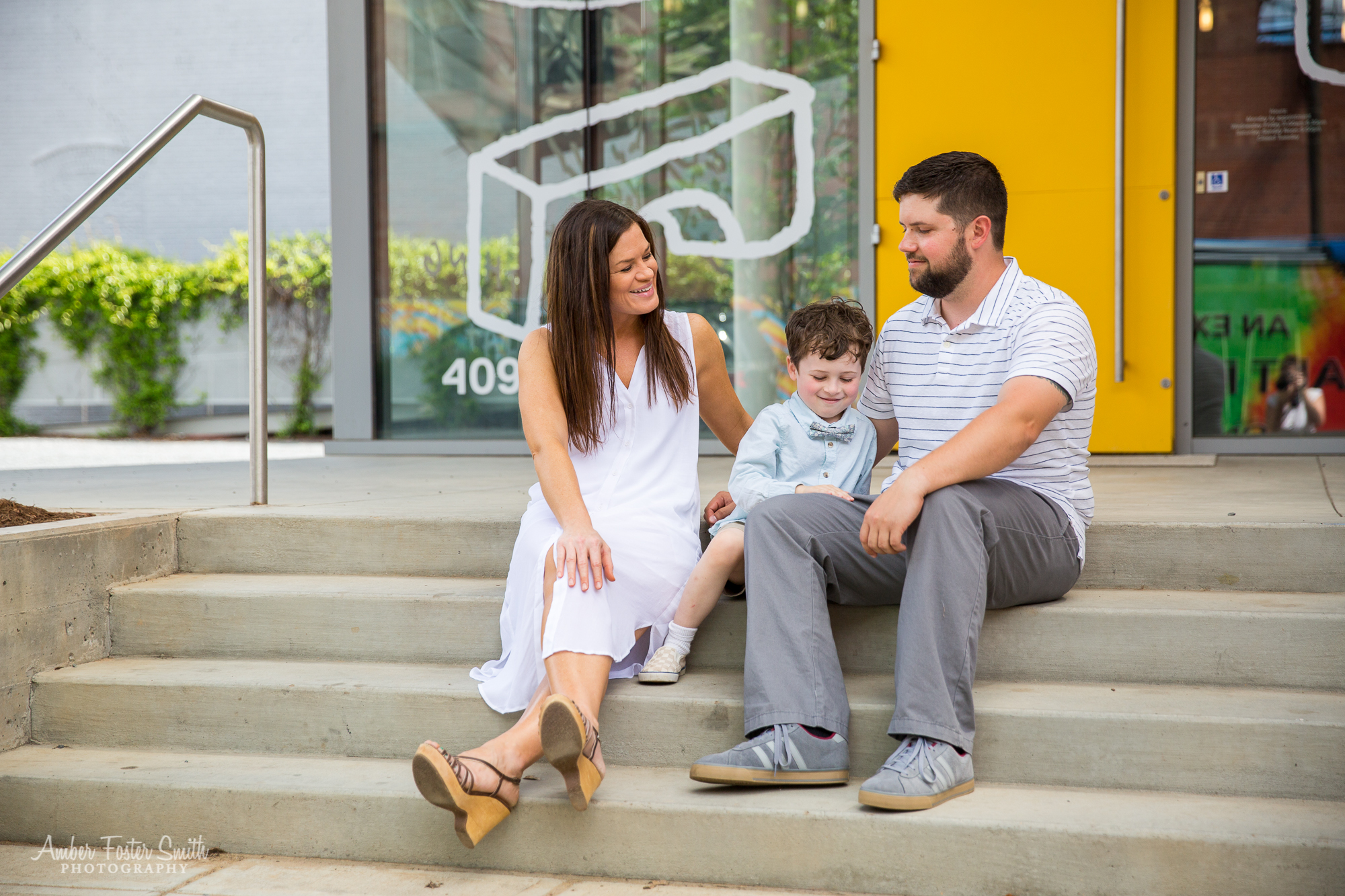 family sitting on steps in front of modern building