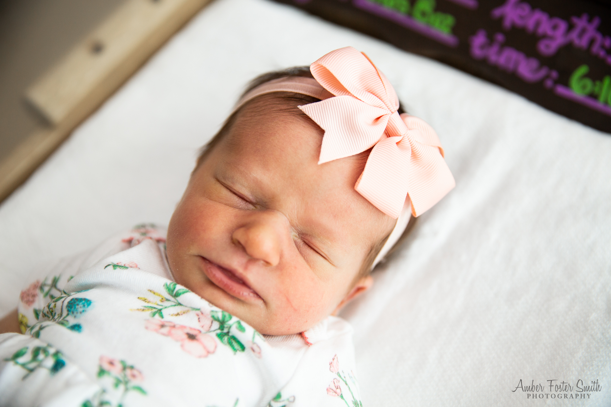 newborn baby wrapped in a blanket with a bow headband