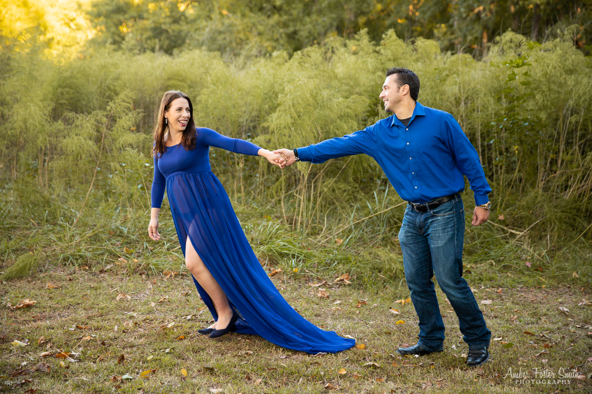Pregnant woman in a long blue dress holding a mans hand and pulling him