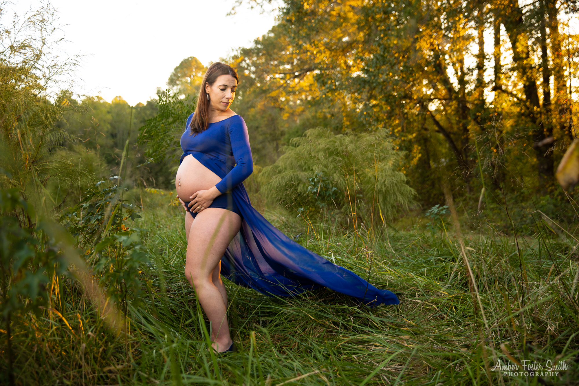 Pregnant woman in long blue dress in field