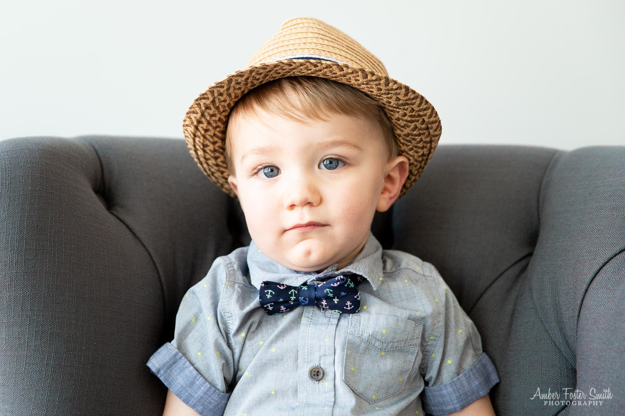 one year old boy in hat sitting
