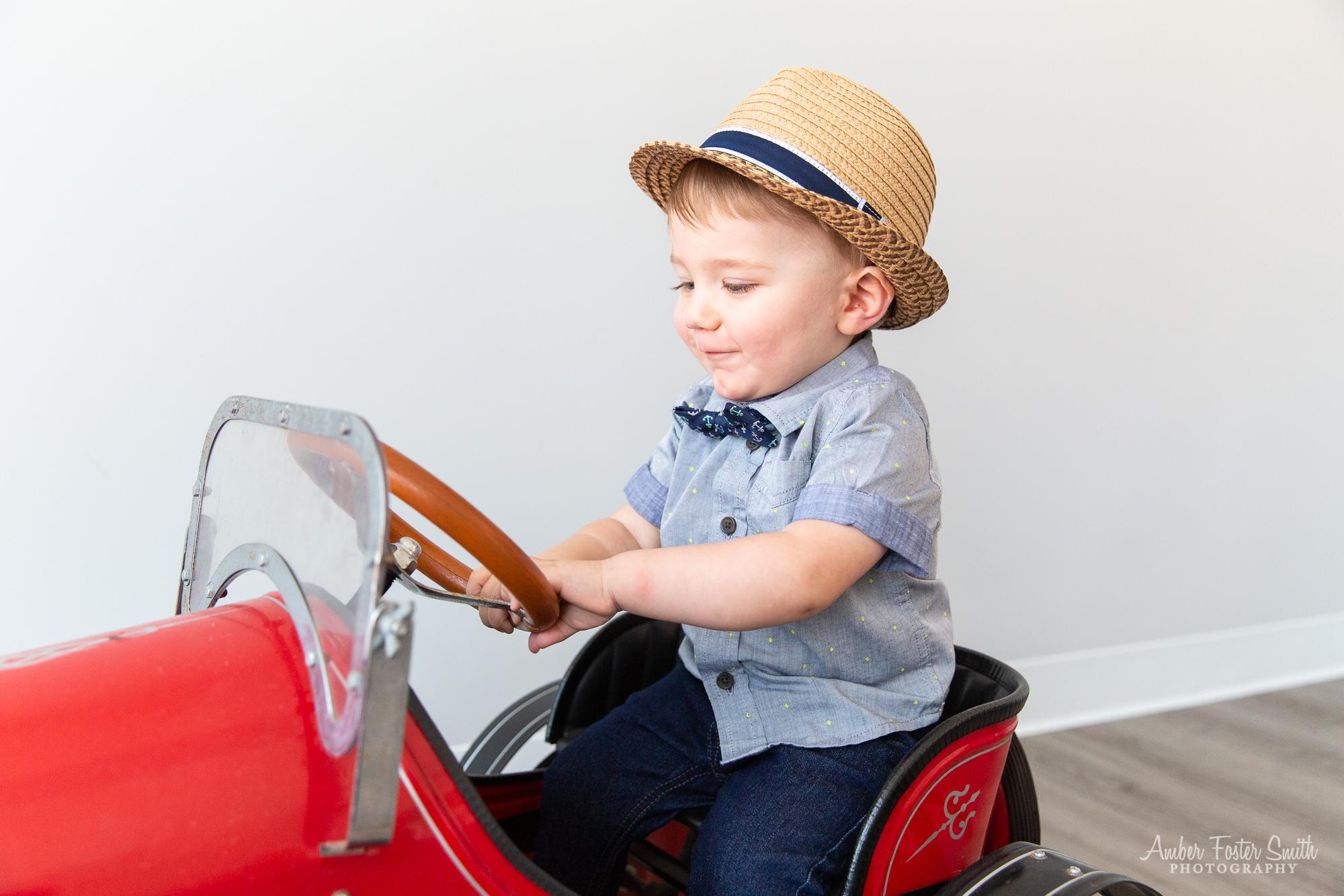 little boy sitting in red car